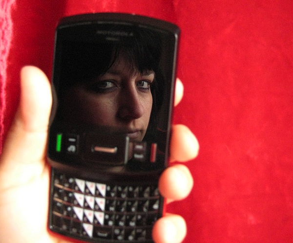 woman holding cell phone in hand using the screen as a mirror