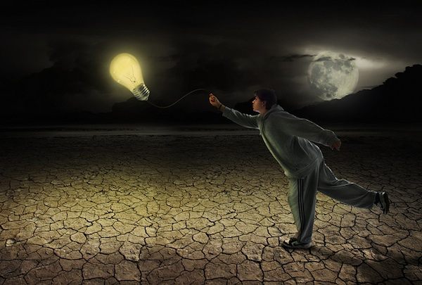 person holding lightbulb kite in desert at night