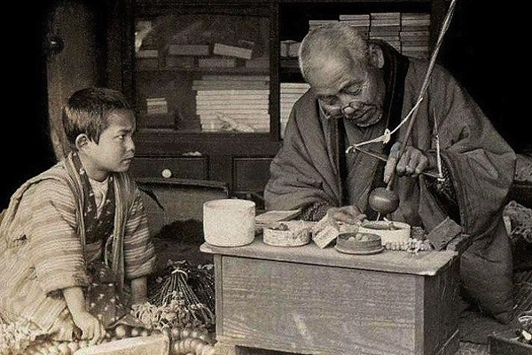 old photograph of elder teaching young boy to make object apprenticeship