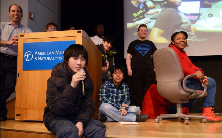 students sitting down on stage giving presentation