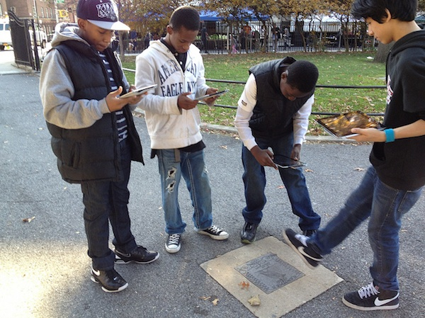 4 boys all taking photo with phones of sidewalk memorial