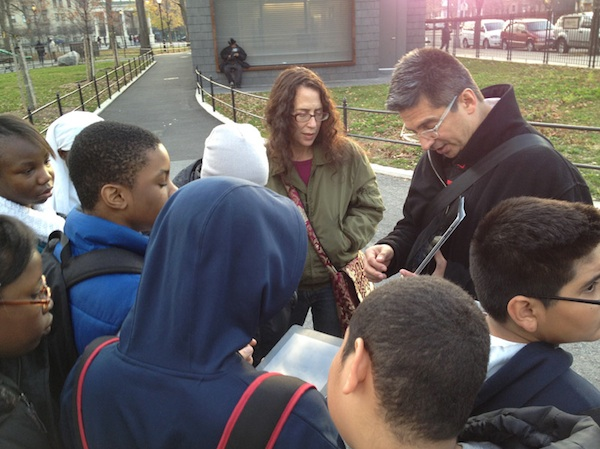 teachers holding ipads instructing students outside