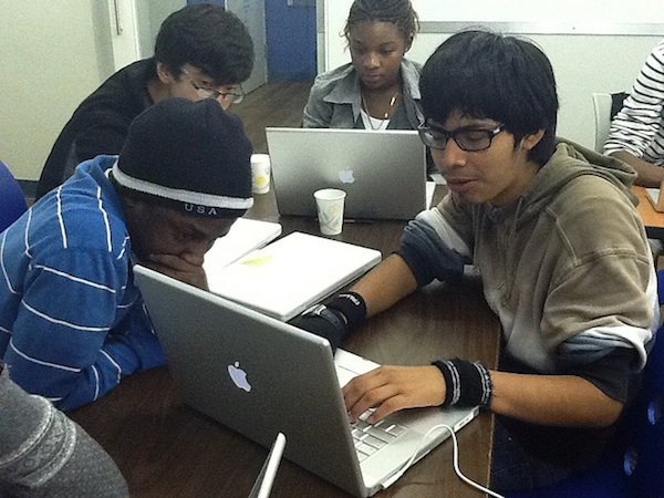 5 students working on laptops together in classroom