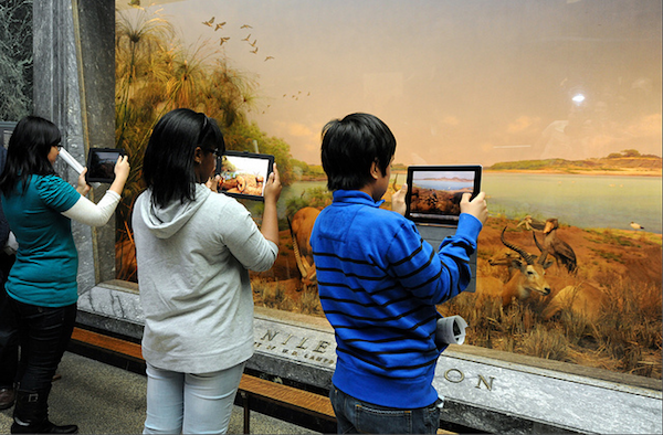 3 kids looking through ipads at museum exibit taking pictures