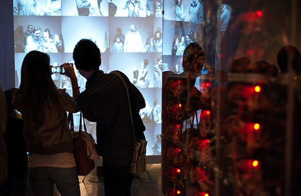 2 young people taking photo of digital screen projection on museum wall