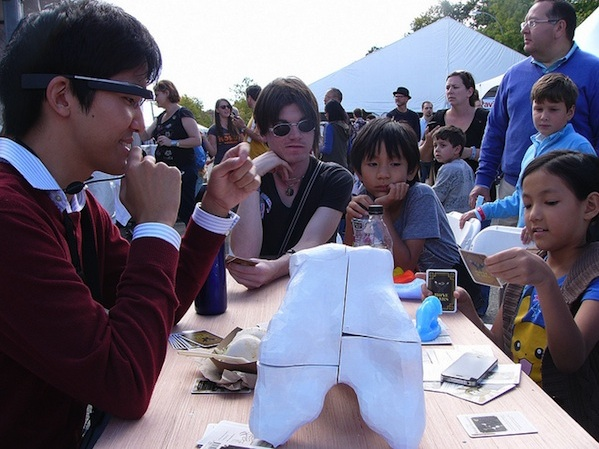 adult and child playing card game outside with google glasses