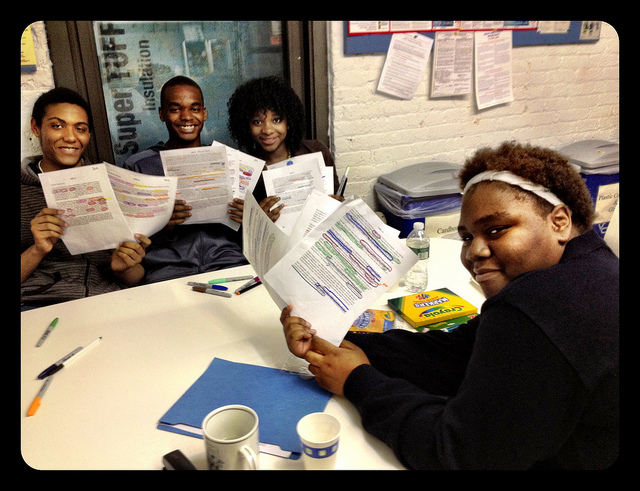 4 students smiling holding up writing paperwork with edits marked on it