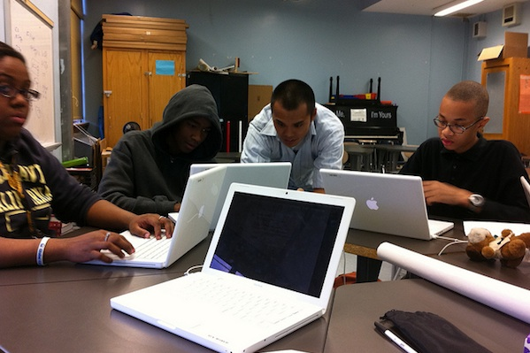group of students sitting around a table working on laptops