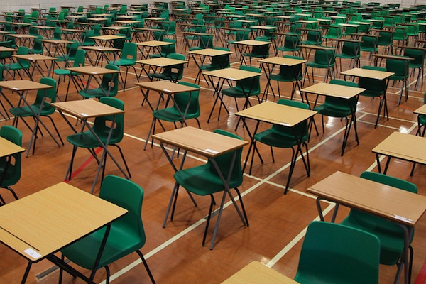 rows of empty green desks in gymnasium