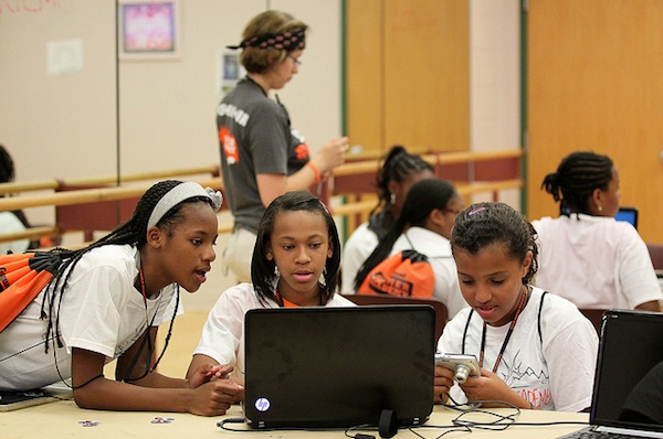 3 black female students gathered around a laptop and camera