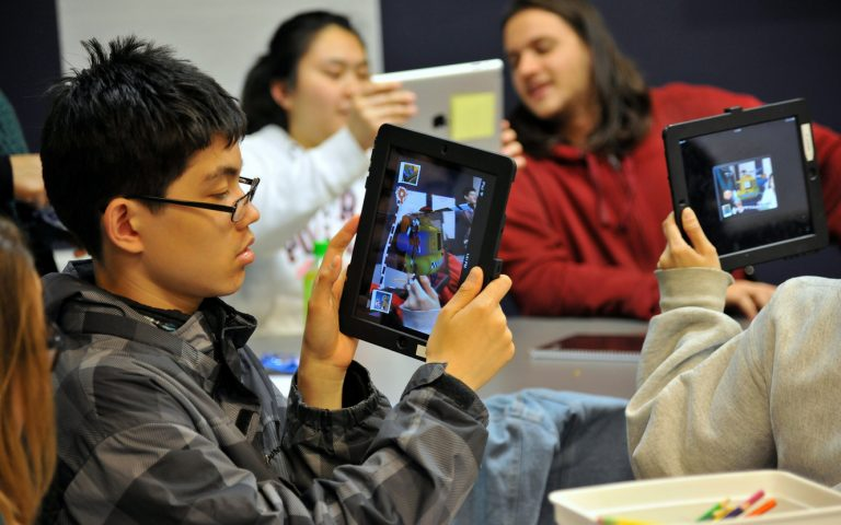 student in classroom taking picture on ipad of another student holding an ipad
