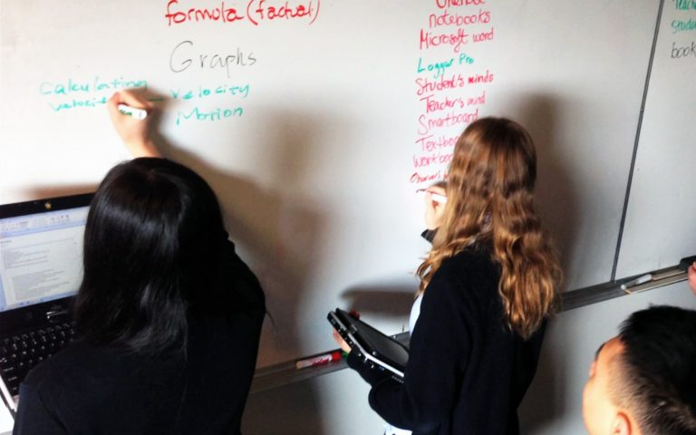 2 female students holding computers writing formulas on whiteboard