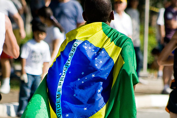 young boy walking in crowd wearing brazil flag on his back