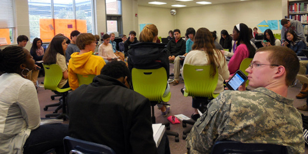 classroom of teenage students sitting in circle of chairs learning