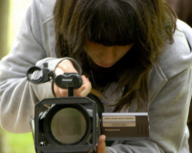 female student holding video camera