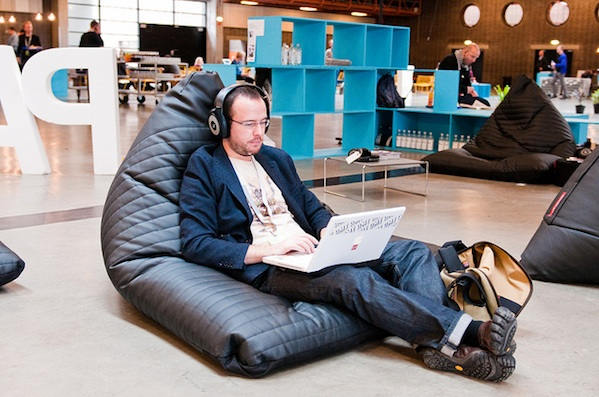 man sitting in shared work space working on laptop sitting on beanbag chair