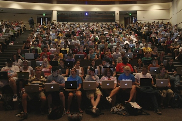 packed college lecture hall of students with laptops