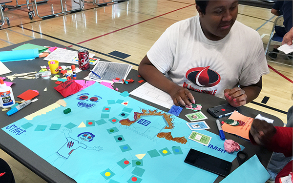 young black student making a game out of posters and crafts in classroom