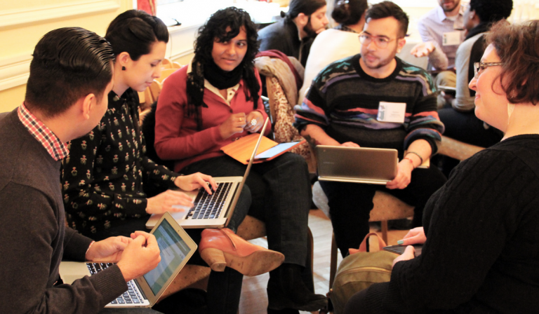 group of adults sitting in circle  on laptops at connected learning research meeting
