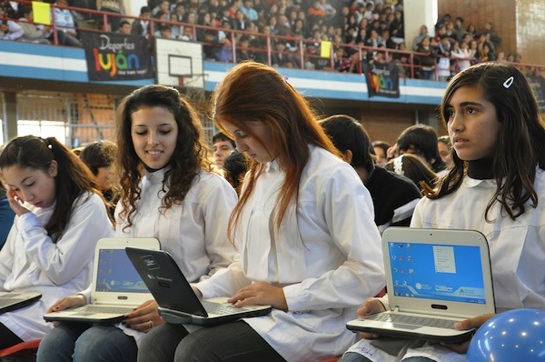 hundreds of girls sitting in auditorium assembly holding computers