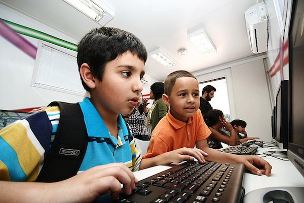 2 kids focused working on computer together in classroom