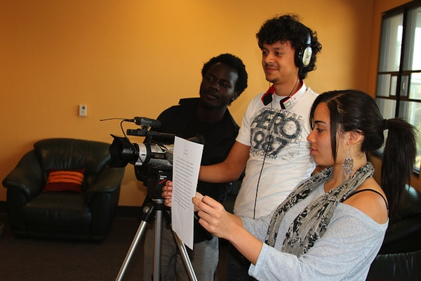 3 students filming video and holding script