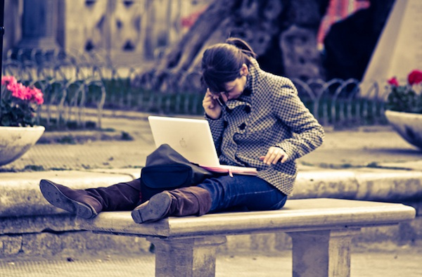 woman sitting on bench in park working on her computer phone