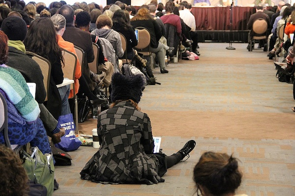 women sitting in the aisle of packed DML conference room