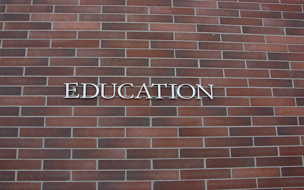 word education on brick building wall