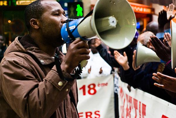 man speaking into loudspeaker  at rally
