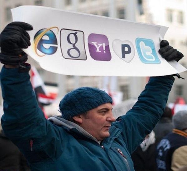 man holding up sign saying Egypt using social media icons during protest