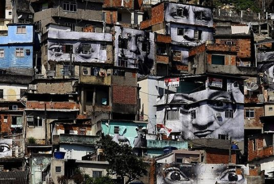 large pictures of human portraits covering front of buildings in poor community