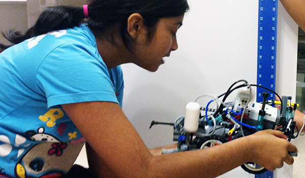young girl working on measuring a robot with another student