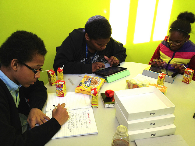 global kids working at table together eating snacks
