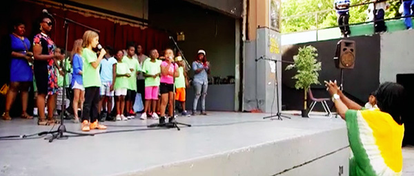 group of kids performing on stage outside with teachers directing