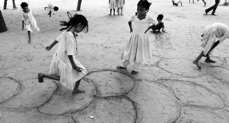 young girls playing hopscotch in the sand