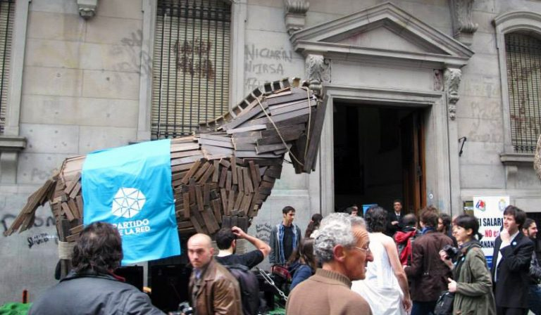 wooden trojan horse outside brick building with large group of people