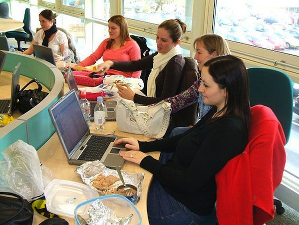 5 women working on laptops around conference table