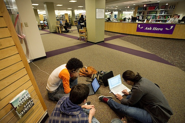 students sitting together in library studying working on computer