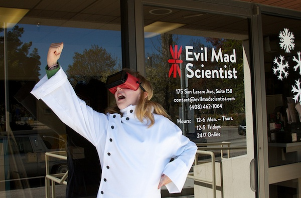 woman in lab coat and virtual reality headset in front of Evil Mad Scientist building