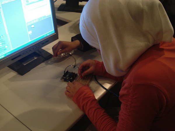 female student working on circuit board at computer desk