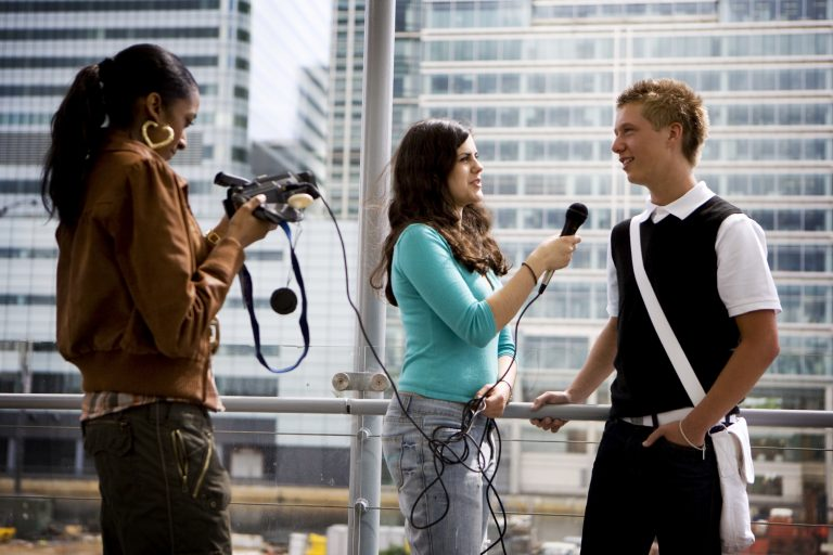 2 female students interviewing a student on camera