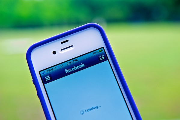 close up of iphone with Facebook loading on screen