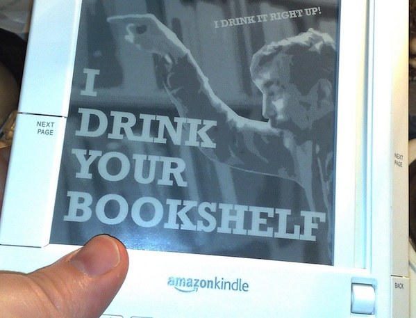hand holding Amazon kindle showing book cover of I drink your bookshelf