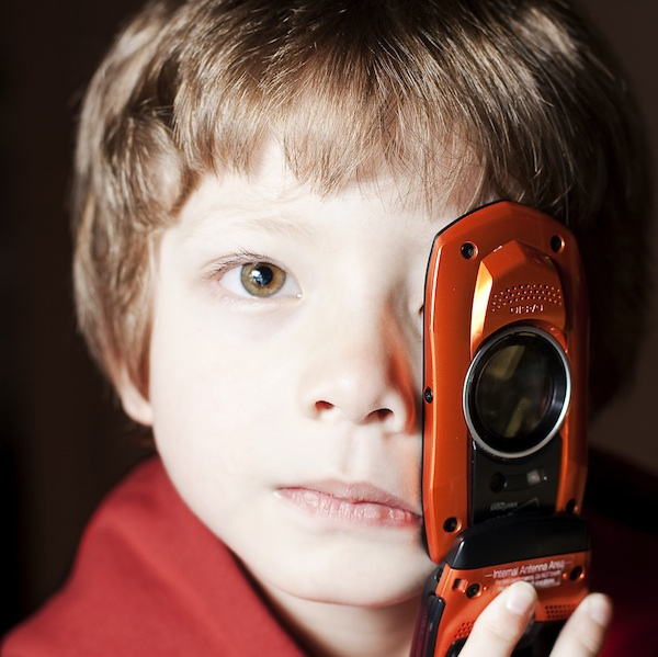young boy holding flip phone over his eye