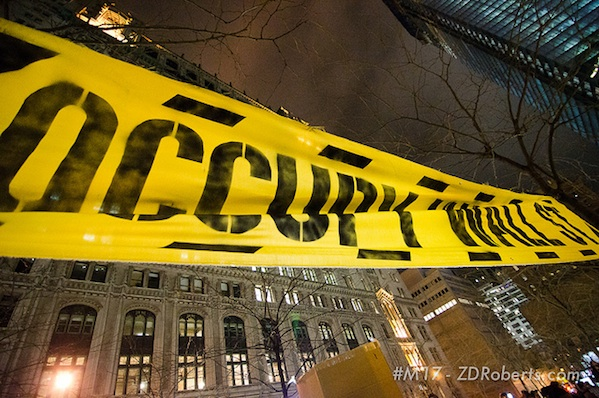 occupy wall street banner on city building