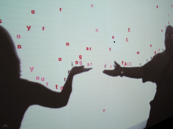 2 peoples shadows projected on wall surrounded by words