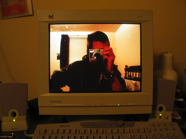 man taking photo of himself displayed on computer screen