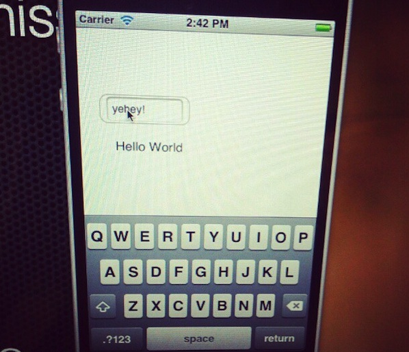 close up of iphone showing keyboard and typed words hello world