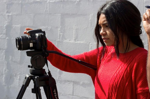 female student filming using camera and tripod against brick wall